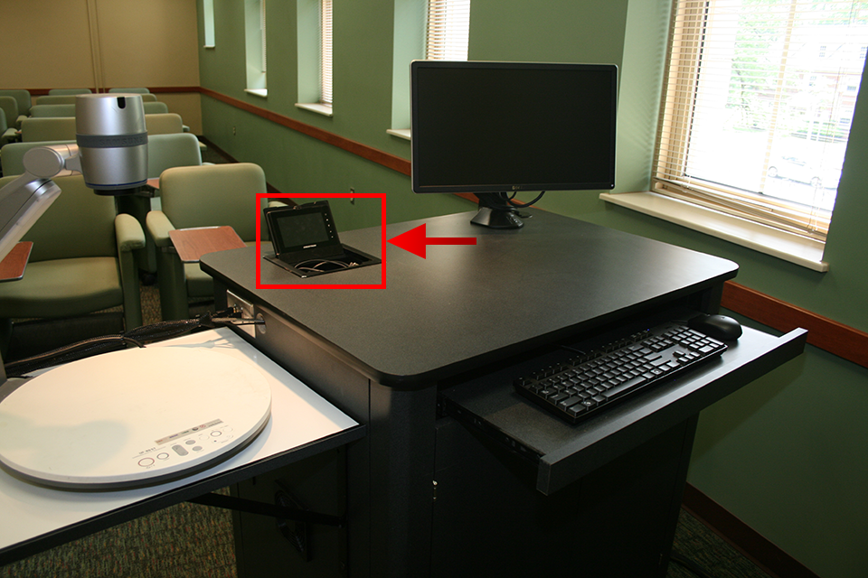 Image indicates location of flip-top touch panel in top-left corner of teacher's station